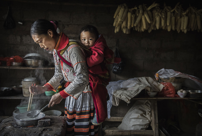 XIAOBATIAN, CHINA - FEBRUARY 7: A woman of the Long Horn Miao ethnic minority group carries a baby on her back as she cooks after Tiaohua or Flower Festival as part of the Lunar New Year  on February 7, 2017 in Xiaobatian village, Guizhou province, southern China. The Long Horn Miao are recognized for their declining practice of wrapping a blend of linen, wool, and the hair of their ancestors around animal horns  or a wooden clip to make headdresses.  Many young women say they now wear the headdresses only for special occasions and festivals, as the ornaments, which are attached by the horns to their real hair, have proved impractical for modern daily life in a fast changing world. China officially recognizes 56 different ethnic minorities, and statistics show over 7 million Chinese identifying themselves as Miao. But the small Long Horn Miao community counts only around 5000 people living in 12 villages, whose age-old traditions, language, and culture are fading. It is increasingly difficult in a modernizing China, as young people are drawn from remote rural villages to opportunities in bigger cities amongst wide-scale urbanization. Farming and labour remain the mainstays of life for the Long Horn Miao, leaving the area relatively poor in comparison with many parts of China. The government has invested significant amounts into local infrastructure and the tourism industry to try to bolster the local economy. (Photo by Kevin Frayer/Getty Images)