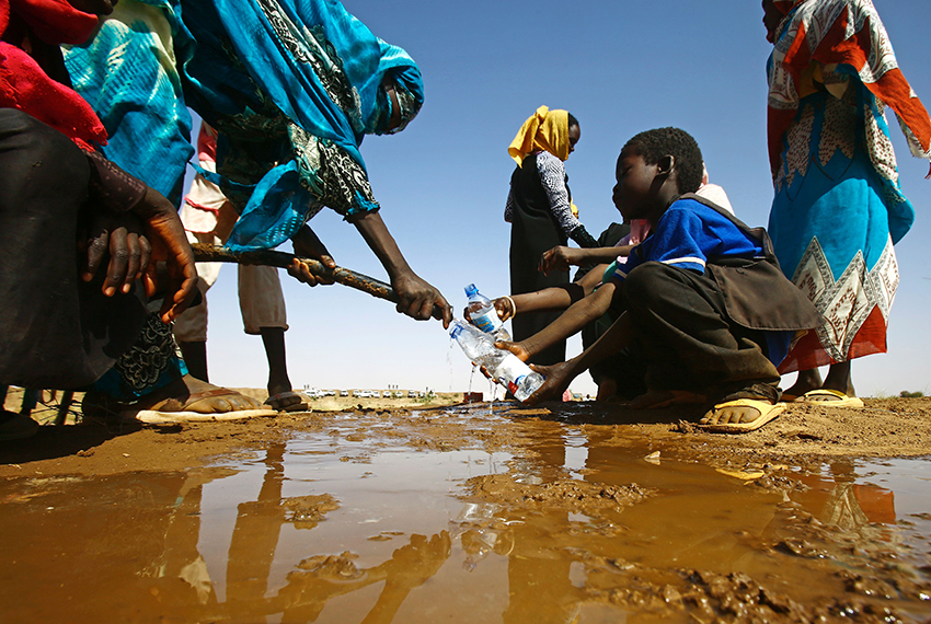 TOPSHOT - A Sudanese woman fills water bottles held by a young boy about 60 kilometres north of El-Fasher, the capital of the North Darfur state, on February 9, 2017.   / AFP / ASHRAF SHAZLY        (Photo credit should read ASHRAF SHAZLY/AFP/Getty Images)