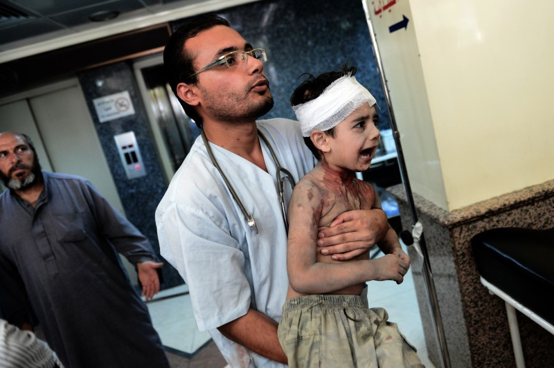 A doctor carries a young wounded boy at a hospital in Syria's northern city of Aleppo, who was injured when a shell, released by regime forces, hit his house on August 24, 2012. Syrian forces blitzed areas in and around the Aleppo , activists said, as Western powers sought to tighten the screws on embattled President Bashar al-Assad.  AFP PHOTO / ARIS MESSINIS        (Photo credit should read ARIS MESSINIS/AFP/GettyImages)