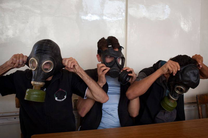 TO GO WITH AFP STORY BY ALBERT GONZALEZ FARRAN Volunteers put on gas masks during a class on how to respond to a chemical attack, in the northern Syrian city of Aleppo on September 15, 2013. For two months, Mohammad Zayed, an Aleppo University student, has been training a group of 26 civilians in the hope they can respond to a chemical attack.  AFP PHOTO / JM LOPEZ        (Photo credit should read JM LOPEZ/AFP/Getty Images)