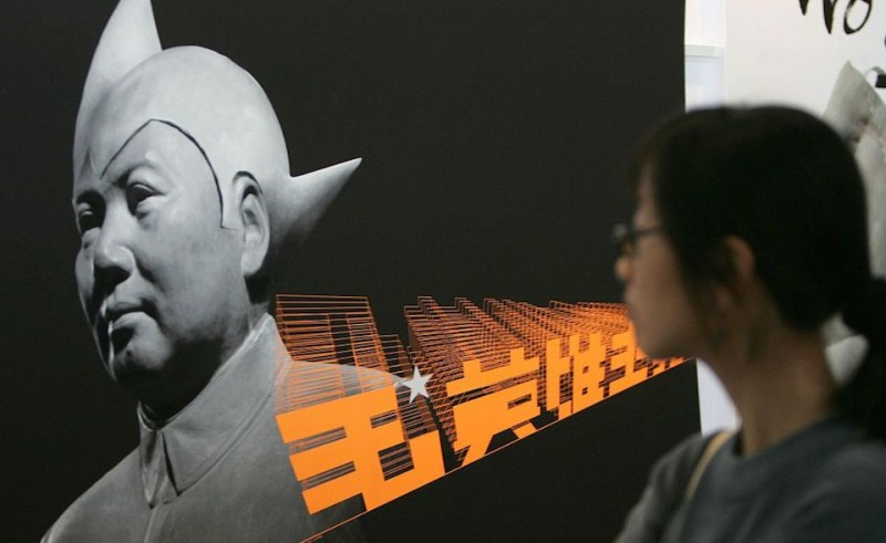 A woman looks at a portrait of futuristic rendition of late Chinese leader Mao Zedong displayed at the design and Innovation exhibition as part of Small and Medium Enterprise (SME) expo at the Convention and Exhibition center in Hong Kong, 21 November 2005.  Hong Kong's jobless rate continued to drop at 5.3 percent for the three months to October, with employment outstripping labour force growth, official figures showed 17 November. The expo will start 21 November.    AFP PHOTO/TED ALJIBE / AFP / TED ALJIBE        (Photo credit should read TED ALJIBE/AFP/Getty Images)