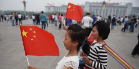 Children pose for photos with the Chinese national flag in Beijing's Tiananmen Square on the May Day national holiday on May 1, 2015. AFP PHOTO / GREG BAKER        (Photo credit should read GREG BAKER/AFP/Getty Images)