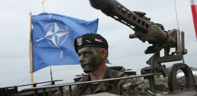 ZAGAN, POLAND - JUNE 18:  A soldier of the Polish Army sits in a tank as a NATO flag flies behind during the NATO Noble Jump military exercises of the VJTF forces on June 18, 2015 in Zagan, Poland. The VJTF, the Very High Readiness Joint Task Force, is NATO's response to Russia's annexation of Crimea and the conflict in eastern Ukraine. Troops from Germany, Norway, Belgium, Poland, Czech Republic, Lithuania and Belgium were among those taking part today.  (Photo by Sean Gallup/Getty Images)