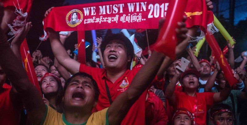 YANGON, MYANMAR - NOVEMBER 09:  A man holds up a sign stating 'we must win' as crowds gather for the election result announcement in front of the National League for Democracy's headquarters after Myanmar's first free and fair election on November 9, 2015 in Yangon, Myanmar. The elections are Myanmar's first openly contested polls in 25 years, following decades of military rule. Noble laureate Aung San Suu Kyi appeared poised to win power in Myanmar on today despite her party's growing concerns about cheating in yesterday's historic election.  (Photo by Lauren DeCicca/Getty Images)