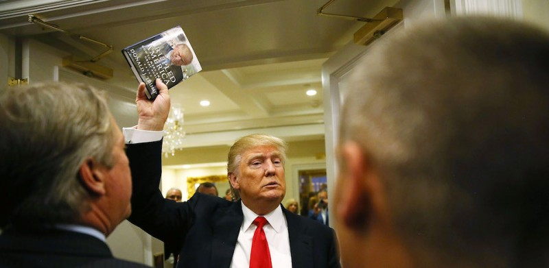 JUPITER, FL - MARCH 08:  Republican presidential candidate Donald Trump holds up his book after holding a press conference at the Trump National Golf Club Jupiter on March 8, 2016 in Jupiter, Florida.  Trump is projected to win the Republican Presidential primaries in Mississippi and Michigan. (Photo by Joe Raedle/Getty Images)