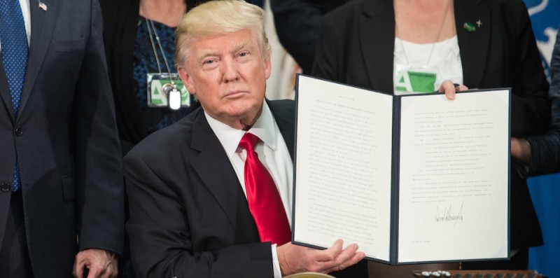 TOPSHOT - US President Donald Trump signs an executive order to start the Mexico border wall project at the Department of Homeland Security facility in Washington, DC, on January 25, 2017. / AFP / NICHOLAS KAMM        (Photo credit should read NICHOLAS KAMM/AFP/Getty Images)