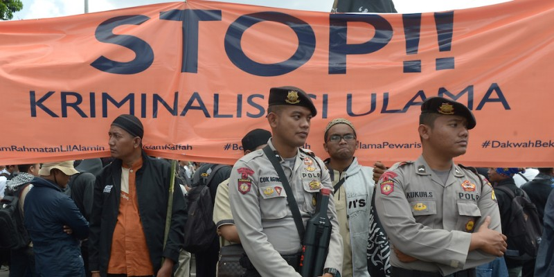 "CORRECTION - Indonesian police stand guard as Muslim protesters hold a rally in support of the country's clerics at the National Monument in Jakarta on February 5, 2017. Hundreds of protesters from the radical Hizbut Tahrir Indonesia (HTI) held a peaceful protest to support Indonesian clerics, including Rizieq Shihab, leader of the FPI (Front Pembela Islam) or Islamic Defending Front, which recently helped organise mass rallies against Jakarta governor and ethnic Chinese Christian Basuki Tjahaja Purnama, who is on trial for allegedly insulting Islam. / AFP / ADEK BERRY / The erroneous mention[s] appearing in the metadata of this photo by ADEK BERRY has been modified in AFP systems in the following manner: [clarifying first sentence to ""supporting clerics"", and correcting the second sentence]. Please immediately remove the erroneous mention[s] from all your online services and delete it (them) from your servers. If you have been authorized by AFP to distribute it (them) to third parties, please ensure that the same actions are carried out by them. Failure to promptly comply with these instructions will entail liability on your part for any continued or post notification usage. Therefore we thank you very much for all your attention and prompt action. We are sorry for the inconvenience this notification may cause and remain at your disposal for any further information you may require.        (Photo credit should read ADEK BERRY/AFP/Getty Images)"