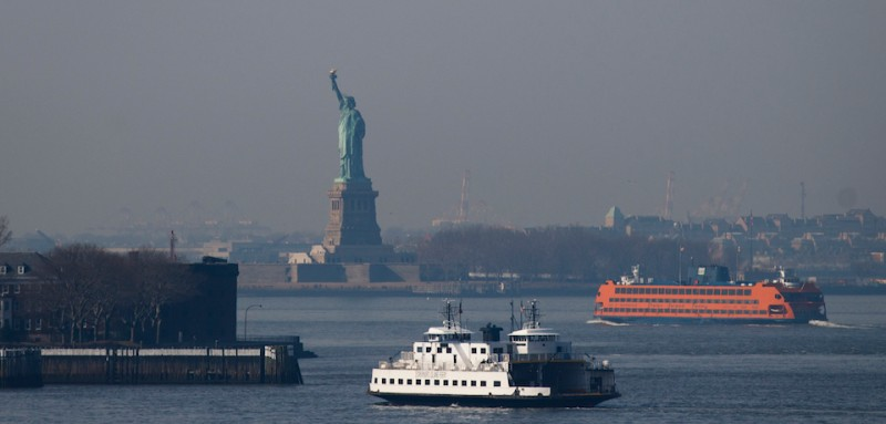 NEW YORK, NY - FEBRUARY 8: (L to R) The Governors Island Ferry and the Staten Island Ferry pass the Statue of Liberty in New York Harbor, February 8, 2017 in New York City. As temperatures touched 60 degrees on Wednesday, the city is preparing for up to a foot of snow on Thursday. (Photo by Drew Angerer/Getty Images)