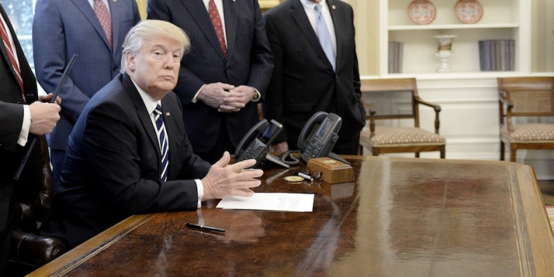 "WASHINGTON, D.C. - FEBRUARY 14:  (AFP-OUT) U.S. President Donald Trump looks on before signing H.J. Res. 41 in the Oval Office of the White House on February 14, 2017 in Washington, DC. The resolution nullifies a rule in the Dodd-Frank Act that ""requires resource extraction issuers to disclose payments made to governments for the commercial development of oil, natural gas, or minerals."" (Photo by Olivier Douliery-Pool/Getty Images)"