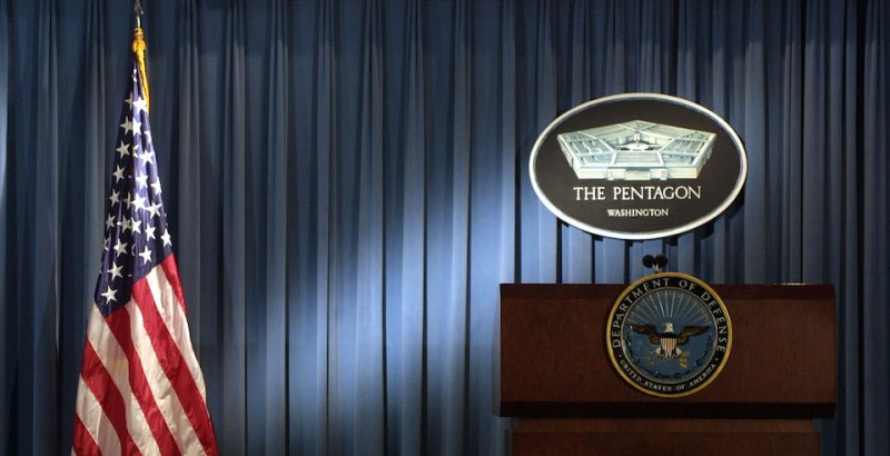 The Pentagon logo and an American flag are lit up in the briefing room of the Pentagon in Arlington, Virginia, on Jan. 3, 2002.