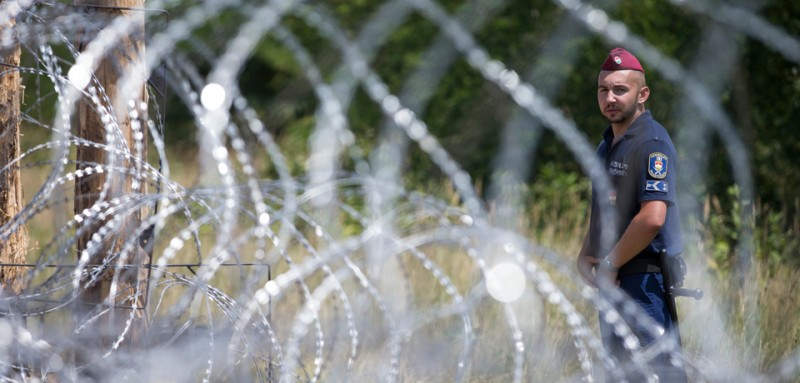 SZEGED, HUNGARY - JULY 16: A Hungarian soldier stands next to the first portion of a temporary fence the Hungarian military is erecting on its border to Serbia in an effort to keep out refugees on July 16, 2015 at Morahalom near Szeged, Hungary. Hungary has become one of the main crossing points, especially for refugees from Syria, Afghanistan and Iraq, who arrive to Europe via Greece and travel through Serbia and Hungary on their way to countries in northern Europe like Germany and Sweden. (Photo by Arpad Kurucz/Getty Images)