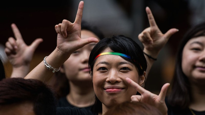 Runners of the Shanghai Pride Run make signs with their fingers while wearing rainbow shoelaces at the start of the race in Shanghai on June 18, 2016. The LGBT festival, Shanghai PRIDE 2016, which celebrates diversity in the Chinese city under this year's theme 'I Am Me', kicked-off with a fun run and will last from June 17 to 26. / AFP / JOHANNES EISELE        (Photo credit should read JOHANNES EISELE/AFP/Getty Images)