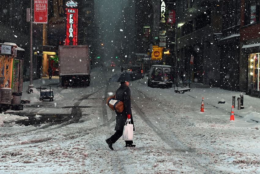 TOPSHOT - People walk the snow and sleet-covered streets of New York on March 14, 2017. Winter Storm Stella unleashed its fury on much of the northeastern United States on March 14 dropping snow and sleet across the region and leading to school closures and thousands of flight cancellations. Stella, the most powerful winter storm of the season, was forecast to dump up to two feet (60 centimeters) of snow in New York and whip the area with combined with winds of up to 60 miles per hour (95 kilometers per hour), causing treacherous whiteout conditions. But after daybreak the National Weather Service (NWS) revised down its predicted snow accumulation for the city of New York, saying that the storm had moved across the coast.  / AFP PHOTO / Jewel SAMAD        (Photo credit should read JEWEL SAMAD/AFP/Getty Images)