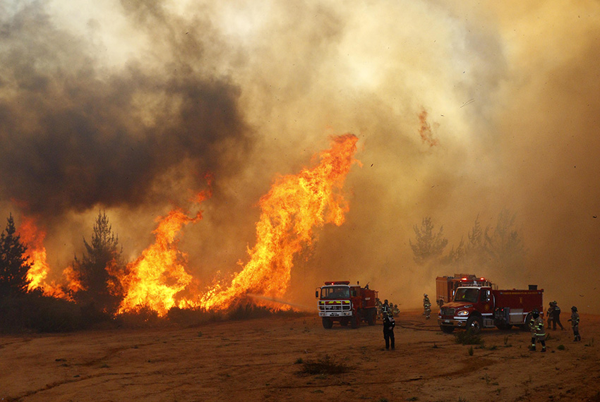 """TOPSHOT - Picture released on March 12, 2017 by Aton Chile shows firefighters working to put out a forest fire in Valparaiso. Chilean authorities decreed red alert in Valparaiso and Vina del Mar for several forest fires. / AFP PHOTO / ATON CHILE / Raul ZAMORA / Chile OUT / RESTRICTED TO EDITORIAL USE - MANDATORY CREDIT """"AFP PHOTO / ATON CHILE / Raúl ZAMORA /HO """" - NO MARKETING - NO ADVERTISING CAMPAIGNS - DISTRIBUTED AS A SERVICE TO CLIENTS          (Photo credit should read RAUL ZAMORA/AFP/Getty Images)"""