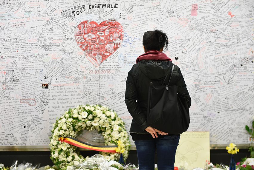 TOPSHOT - A woman stands in front of a remembrance wall on March 22, 2017 at the Maelbeek - Maalbeek subway station in Brussels, during the commemorations marking the first anniversary of the twin Brussels attacks by Islamic extremists. Belgium marks the first anniversary of the Islamic State bombings in Brussels, one at the airport and the other in the metro, in which 32 people were killed and more than 320 wounded with ceremonies showing that the heart of Europe stands defiant. / AFP PHOTO / JOHN THYS        (Photo credit should read JOHN THYS/AFP/Getty Images)