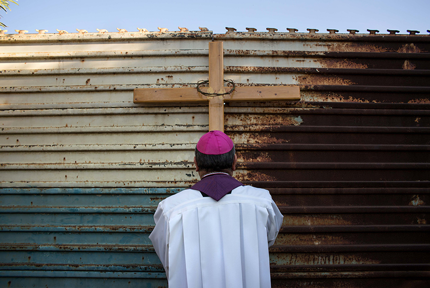 TOPSHOT - Tijuana's Archbishop Francisco Moreno Barron prays for migrants at the US-Mexico border fence in Tijuana, northwestern Mexico on March 19, 2017. / AFP PHOTO / GUILLERMO ARIAS        (Photo credit should read GUILLERMO ARIAS/AFP/Getty Images)