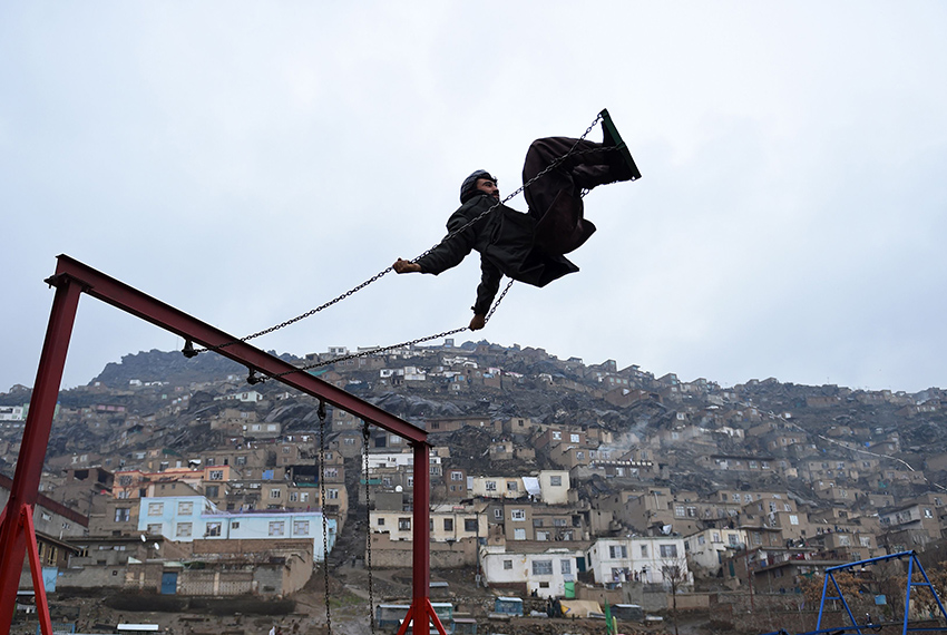TOPSHOT - An Afghan man swings on a swing near the Sakhi Shrine during the Nowruz festival to mark the Afghan New Year in Kabul on March 21, 2017. Nowruz, one of the biggest festivals of the war-scarred nation, marks the first day of spring and the beginning of the year in the Persian calendar. Nowruz is calculated according to a solar calendar, this coming year marking 1396. / AFP PHOTO / WAKIL KOHSAR        (Photo credit should read WAKIL KOHSAR/AFP/Getty Images)