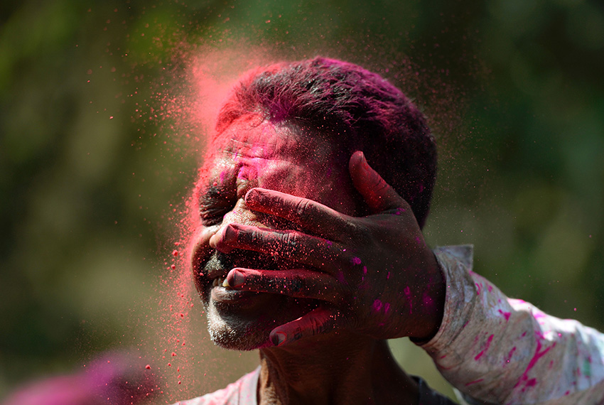TOPSHOT - An Indian man is smeared with coloured powder during the Holi celebrations in Mumbai on March 13, 2017.   Holi, the festival of colours, is a riotous celebration of the coming of spring and falls on the day after full moon annually in March. / AFP PHOTO / PUNIT PARANJPE        (Photo credit should read PUNIT PARANJPE/AFP/Getty Images)