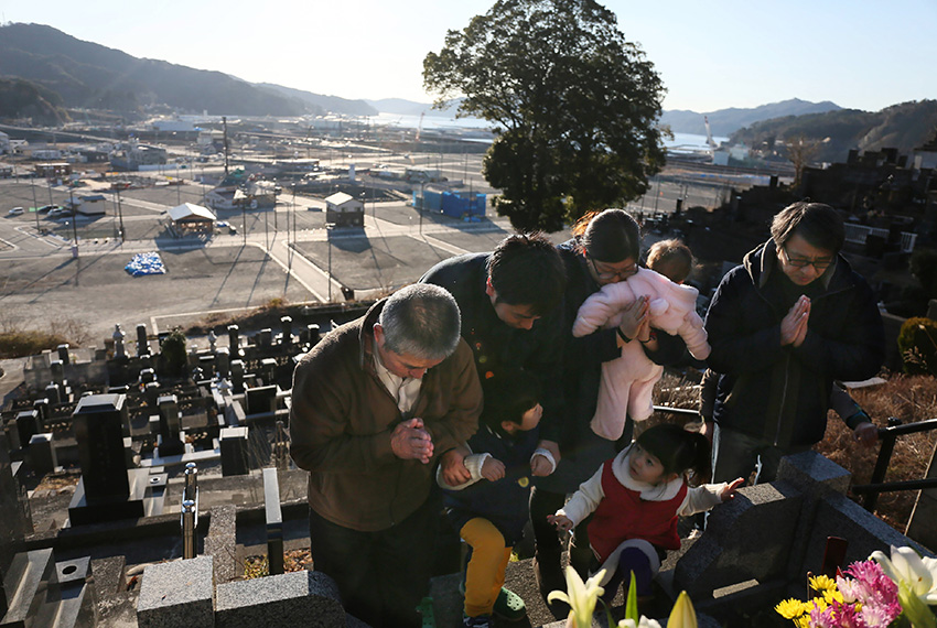 TOPSHOT - Relatives pray while visiting their family's grave at the town of Otsuchi, Iwate prefecture on March 11, 2017. Japan is marking on March 11 the sixth anniversary of the magnitude 9.0 quake which struck under the Pacific Ocean and the ensuing tsunami which left about 18,500 people dead or missing. The massive flow of water overwhelmed cooling systems at the Fukushima Daiichi plant, causing meltdowns in three of its six reactors in what was the worst nuclear disaster since Chernobyl in 1986.  / AFP PHOTO / JIJI PRESS / JIJI PRESS / Japan OUT        (Photo credit should read JIJI PRESS/AFP/Getty Images)