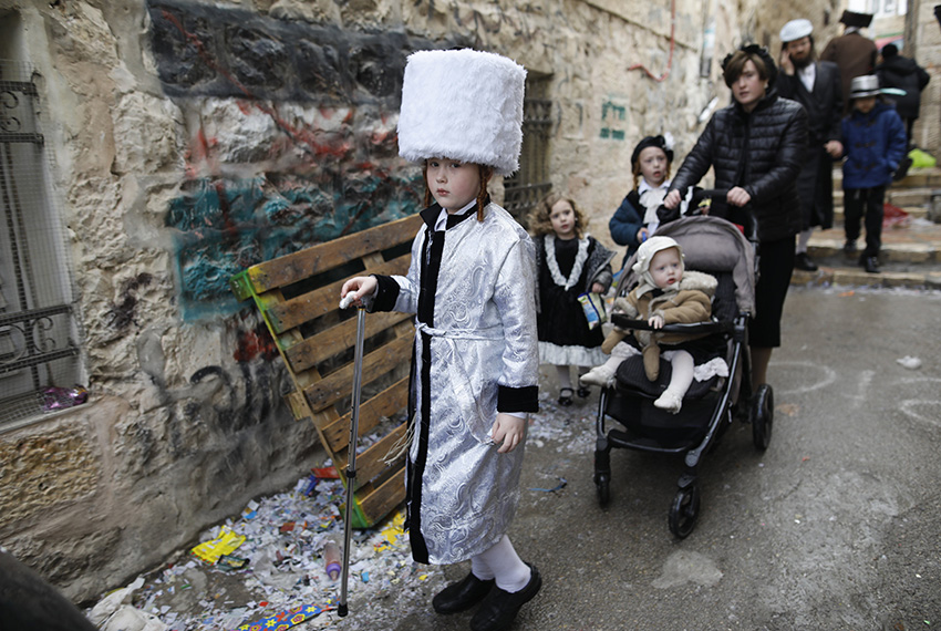 TOPSHOT - Ultra-Orthodox Jewish children wearing costumes walk in Jerusalem's Mea Shearim ultra-Orthodox neighbourhood on March 13, 2017 during the religious holiday of Purim. The carnival-like Purim holiday is celebrated with parades and costume parties to commemorate the deliverance of the Jewish people from a plot to exterminate them in the ancient Persian Empire 2,500 years ago, as recorded in the Biblical Book of Esther. / AFP PHOTO / MENAHEM KAHANA        (Photo credit should read MENAHEM KAHANA/AFP/Getty Images)