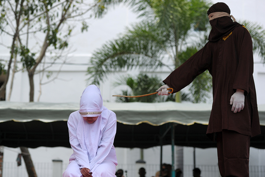 TOPSHOT - An Acehnese woman gets whipped for spending time in close proximity with a man who is not her husband, which is against Sharia law, in Aceh on March 20, 2017.   Aceh on Sumatra island began implementing Sharia law after being granted special autonomy in 2001, an attempt by the central government in Jakarta to quell a long-running separatist insurgency. / AFP PHOTO / CHAIDEER MAHYUDDIN        (Photo credit should read CHAIDEER MAHYUDDIN/AFP/Getty Images)