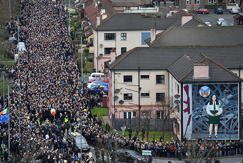 TOPSHOT - Mourners form a funeral procession as they make their way with the coffin past a Republican mural to St Columba's Church Long Tower for the funeral of former Northern Ireland Deputy First Minister Martin McGuinness in Derry, Northern Ireland on March 23, 2017. Former Irish Republican Army commander turned peace negotiator Martin McGuinness divided opinion both in life and in death but on Thursday his supporters gave him the funeral of an Irish chieftain. / AFP PHOTO / BEN STANSALL        (Photo credit should read BEN STANSALL/AFP/Getty Images)