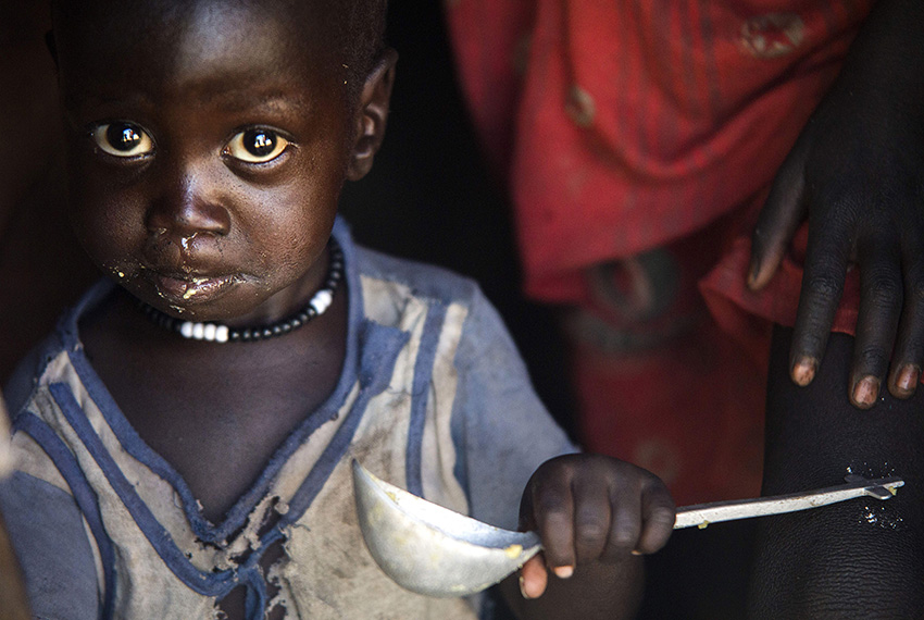 """TOPSHOT - A boy eats out of a ladle at his home in Ngop in South Sudan's Unity State on March 10, 2017. The Norwegian Refugee Council (NRC) distributed food (maize, lentils, oil and corn soya blend) for more than 7,100 people in Ngop. South Sudan, the world's youngest nation formed after splitting from the north in 2011, has declared famine in parts of Unity State, saying 100,000 people face starvation and another million are on the brink of famine. Aid groups have slammed a """"man-made"""" famine caused by ongoing fighting in the country where civil war has forced people to flee, disrupted agriculture, sent prices soaring, and seen aid agencies blocked from accessing some of the worst-hit areas. / AFP PHOTO / ALBERT GONZALEZ FARRAN        (Photo credit should read ALBERT GONZALEZ FARRAN/AFP/Getty Images)"""