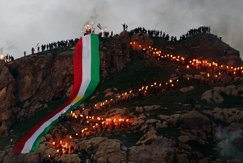 TOPSHOT - Iraqi Kurds holding lit torches walk up a mountain, draped in a large Kurdish flag, in the town of Akra, 500 km north of Baghdad, on March 20, 2017 as they celebrate the Noruz spring festival.  The Persian New Year is an ancient Zoroastrian tradition celebrated by Iranians and Kurds which coincides with the vernal (spring) equinox and is calculated by the solar calender.  / AFP PHOTO / SAFIN HAMED        (Photo credit should read SAFIN HAMED/AFP/Getty Images)