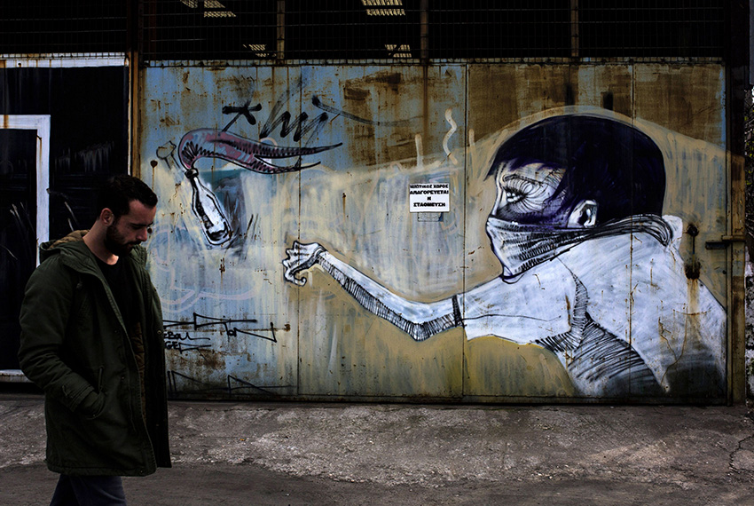 TOPSHOT - A man walks past a graffiti depicting a man throwing a petrol bomb on March 17, 2017 in the Greek capital, Athens. Greek authorities on March 17, 2017 were trying to determine how a near-defunct militant group was able to sneak at least two parcel bombs through airport security, one of which exploded at the IMF offices in Paris. The investigation so far suggests that the booby-trapped mail sent to the IMF and the German finance ministry -- presumably by a far-left group called the Conspiracy of Fire Nuclei -- failed to raise an alarm because it contained only a small amount of gunpowder.  / AFP PHOTO / Angelos Tzortzinis        (Photo credit should read ANGELOS TZORTZINIS/AFP/Getty Images)