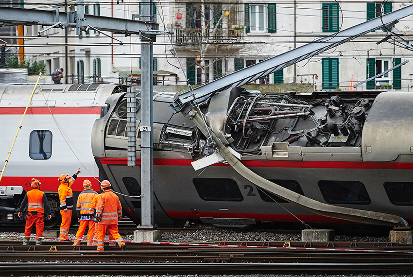TOPSHOT - Police officers and workers inspect the site of a train crash at the train station of Lucerne where a Eurocity train of Trenitalia derailed on March 22, 2017 in Lucerne.  / AFP PHOTO / Michael Buholzer        (Photo credit should read MICHAEL BUHOLZER/AFP/Getty Images)