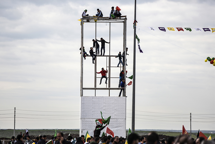 TOPSHOT - Young men climb or sit on a scaffolding as Turkish Kurds gather for Newroz celebrations for the new year in Diyarbakir, southeastern Turkey, on March 21, 2017. Newroz (also known as Nawroz or Nowruz) is an ancient Persian festival, which is also celebrated by Kurdish people, marking the first day of spring, which falls on March 21.  / AFP PHOTO / BULENT KILIC        (Photo credit should read BULENT KILIC/AFP/Getty Images)