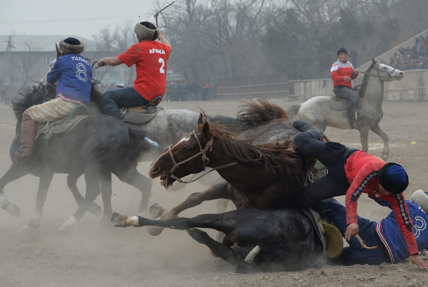 """TOPSHOT - Kyrgyz riders play the traditional Central Asian sport of Kok-Boru (Gray Wolf) or Buzkashi (Goat Grabbing) during celebrations for Nowruz in Bishkek on March 16, 2017. Mounted players compete for points by throwing a stuffed sheepskin into a well. Nowruz, """"The New Year"""" in Farsi, is an ancient festival marking the first day of spring in Central Asia. / AFP PHOTO / Vyacheslav OSELEDKO        (Photo credit should read VYACHESLAV OSELEDKO/AFP/Getty Images)"""