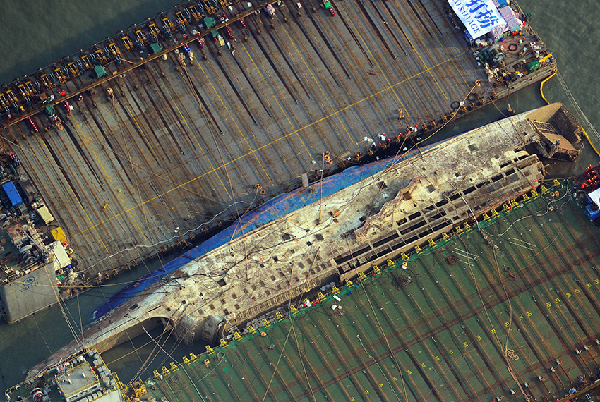 TOPSHOT - This aerial image shows part of the damaged Sewol ferry between two barges after being raised during a salvage operation at sea off the southwestern island of Jindo on March 23, 2017. South Koreas sunken Sewol ferry emerged from the waters on March 23, nearly three years after it went down with the loss of more than 300 lives and dealt a crushing blow to now-ousted president Park Geun-Hye. / AFP PHOTO / STRINGER        (Photo credit should read STRINGER/AFP/Getty Images)