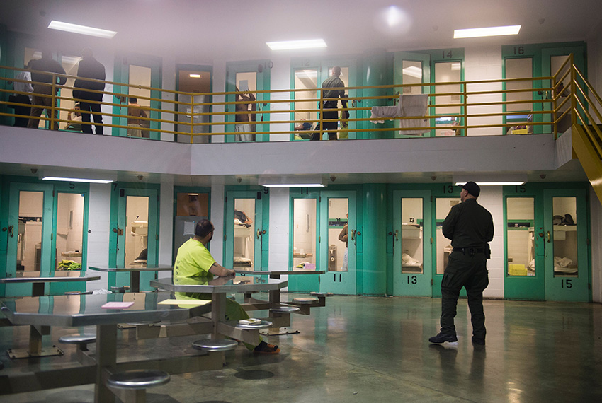 TOPSHOT - A sheriff's deputy (R) talks to an immigration detainee (L) in a high security housing unit at the Theo Lacy Facility, a county jail which also houses immigration detainees arrested by the US Immigration and Customs Enforcement  (ICE), March 14, 2017 in Orange, California, about 32 miles (52km) southeast of Los Angeles.    US President Donald Trumps first budget provides more than USD 4.5 billion in new spending to fight illegal immigration by adding immigration and border enforcement agents, prosecutors and judges, as well as building a wall on the border with Mexico. / AFP PHOTO / Robyn Beck        (Photo credit should read ROBYN BECK/AFP/Getty Images)