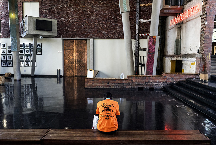 TOPSHOT - An activist from Black Sash, a South African human rights NGO, waits in the hall at the Constitutional Court on March 17, 2017, in Johannesburg as he waits for a ruling of the Court to resolve the social grant payment crisis in South Africa, two weeks before the current deal expires.  / AFP PHOTO / MARCO LONGARI        (Photo credit should read MARCO LONGARI/AFP/Getty Images)