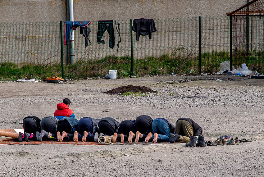"TOPSHOT - Iraqi Kurds migrants pray in La Liniere camp in Grande-Synthe, northern France, on March 21, 2017 where about 1,400-1,500 people stay.  The number of people staying in the Grande-Synthe camp has swelled to about 1,400-1,500 since the destruction last October of the squalid so-called ""Jungle"" camp along the coast near Calais. / AFP PHOTO / PHILIPPE HUGUEN        (Photo credit should read PHILIPPE HUGUEN/AFP/Getty Images)"