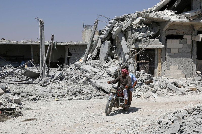 "A Syrian man rides his motorcycle past collapsed buildings in the northern Syrian town of Manbij as civilians go back to their homes on August 14, 2016 more than a week after the Arab-Kurdish alliance, known as the Syrian Democratic Forces (SDF), pushed the Islamic State (IS) group out of the city. The last remaining IS fighters abandoned the city of Manbij near the Turkish border on August 12, 2016 after a rout the Pentagon said showed the extremists were ""on the ropes"". The retreat from the city which IS captured in 2014 was the jihadists' worst defeat yet at the hands of the SDF backed by US air power. / AFP / DELIL SOULEIMAN        (Photo credit should read DELIL SOULEIMAN/AFP/Getty Images)"