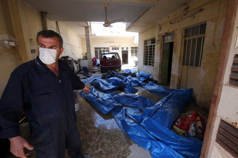 An Iraqi rescue worker gestures towards bodies wrapped in plastic in the Mosul al-Jadida area on March 26, 2017, following air strikes in which civilians have been reportedly killed during an ongoing offensive against the Islamic State (IS) group.   Iraq is investigating air strikes in west Mosul that reportedly killed large numbers of civilians in recent days, a military spokesman said.  / AFP PHOTO / AHMAD AL-RUBAYE        (Photo credit should read AHMAD AL-RUBAYE/AFP/Getty Images)