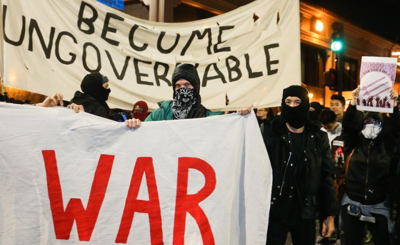 BERKELEY, CA - FEBRUARY 1: People protesting controversial Breitbart writer Milo Yiannopoulos take to the streets on February 1, 2017 in Berkeley, California. A scheduled speech by Yiannopoulos was cancelled after protesters and police engaged in violent skirmishes. (Photo by Elijah Nouvelage/Getty Images)