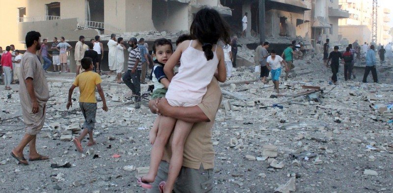 "A man carries two children away from the scene of an explosion in the northern Syrian city of Raqqa, early on August 7, 2013. UN weapons inspectors tasked with looking into claims of chemical weapons use in Syria are ""completing their preparations"" in The Hague before heading to Damascus, the United Nations said. AFP PHOTO/ABDULLAH AL-SHAM        (Photo credit should read ABDULLAH AL-SHAM/AFP/Getty Images)"