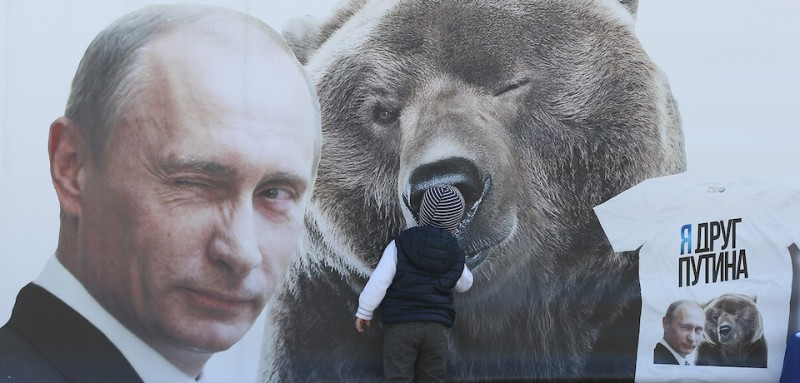 "MOSCOW, RUSSIA - MAY 08:  A little boy inspects a billboard showing a winking Russian President Vladimir Putin and a bear as well as a t-shirt that reads: ""I'm a friend of Putin"" at Victory Park ahead of celebrations to mark the 70th anniversary of the victory over Nazi Germany and the end of World War II on May 8, 2015 in Moscow, Russia. The city of Moscow will celebrate the anniversary on May 9 with a Victory Day international military parade and other events that most European leaders are snubbing because they accuse Russia of involvement in the war in eastern Ukraine.  (Photo by Sean Gallup/Getty Images)"
