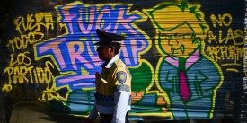 """TOPSHOT - A policeman walks in front of a graffiti against US President Donald Trump in Mexico City during his inauguration on January 20, 2017. Billionaire outsider Donald Trump was sworn in on Friday as the 45th president of the United States and announced that he will shield the country's borders against immigrants and protect it from the """"ravages"""" of free trade. / AFP / RONALDO SCHEMIDT        (Photo credit should read RONALDO SCHEMIDT/AFP/Getty Images)"""