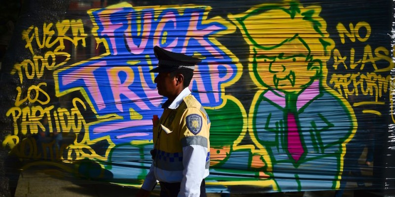 "TOPSHOT - A policeman walks in front of a graffiti against US President Donald Trump in Mexico City during his inauguration on January 20, 2017. Billionaire outsider Donald Trump was sworn in on Friday as the 45th president of the United States and announced that he will shield the country's borders against immigrants and protect it from the ""ravages"" of free trade. / AFP / RONALDO SCHEMIDT        (Photo credit should read RONALDO SCHEMIDT/AFP/Getty Images)"