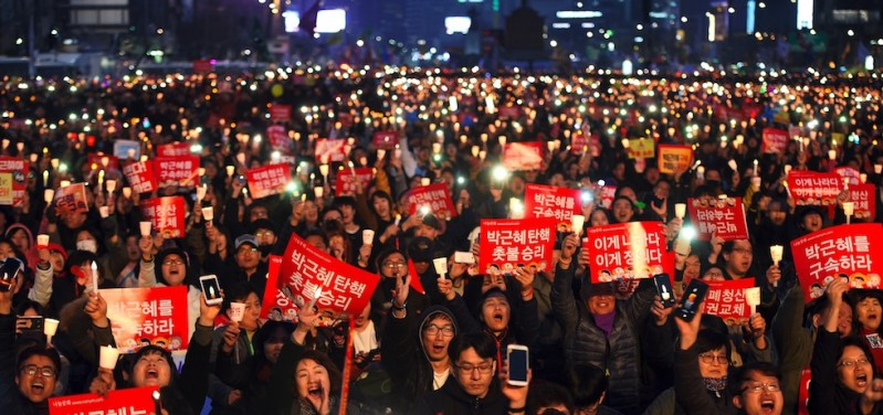 South Korean demonstrators hold up candles during a candlelit rally demanding arrest of Park Geun-Hye in Seoul on March 11, 2017. South Korea's ousted leader Park Geun-Hye was holed up in the presidential Blue House Saturday as protesters took to Seoul's streets demanding her arrest, a day after a court upheld her impeachment. / AFP PHOTO / JUNG Yeon-Je        (Photo credit should read JUNG YEON-JE/AFP/Getty Images)
