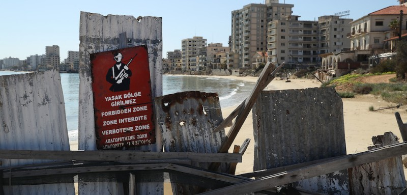 "FAMAGUSTA, CYPRUS - MARCH 06:  Former, decaying hotel buildings stand beyond a makeshift barrier and a Turkish military sign inside the ""Forbidden Zone"" of Varosha district on March 6, 2017 in Famagusta, Cyprus. Hundrds of buildings inside Varosha district, which was once a prime Cypriot resort, stand abandoned and decaying in a zone the Turkish military has sealed off ever since Varosha residents fled in the 1974 war. Cyprus has been divided into a Greek south and Turkish north ever since the brief but devastating war of 1974. Since then United Nations peacekeepers have maintained a buffer zone that runs through the capital city of Nicosia and across the entire island to keep the factions apart. In the south the Greek-dominated Republic of Cyprus is internationally-recognized and a member of the European Union, while in the north the self-proclaimed Turkish Republic of North Cyprus (TRNC) is recognized only by Turkey, which also has tens of thousands of troops stationed there. Negotiations over possible reunification have made strident progress over the last few years, though they have stalled in recent months.  (Photo by Sean Gallup/Getty Images)"