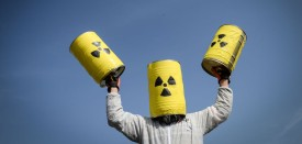 A man carries fake nuclear barrels during a demonstration to demand the closure of Fessenheim nuclear power plant on March 12, 2017 in Fessenheim, eastern France.    / AFP PHOTO / SEBASTIEN BOZON        (Photo credit should read SEBASTIEN BOZON/AFP/Getty Images)