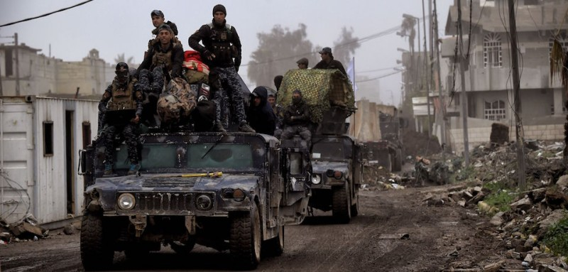 Members of the Iraqi forces drive their Humvees in the streets of west Mosul on March 17, 2017 as they advance in the offensive against Islamic State (IS) group jihadists. / AFP PHOTO / ARIS MESSINIS        (Photo credit should read ARIS MESSINIS/AFP/Getty Images)