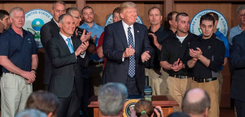 "Surrounded by miners from Rosebud Mining, US President Donald Trump (C) applauds after signing the Energy Independence Executive Order at the Environmental Protection Agency (EPA) Headquarters in Washington, DC, March 28, 2017. President Donald Trump claimed an end to the ""war on coal"" Tuesday, as he moved to roll back climate protections enacted by predecessor Barack Obama. / AFP PHOTO / JIM WATSON        (Photo credit should read JIM WATSON/AFP/Getty Images)"