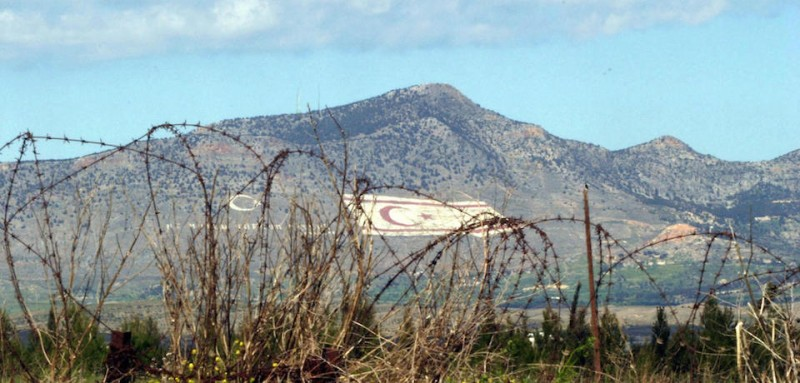 "TO GO WITH STORY BY SOPHIE DEVILLER A huge Turkish-Cypriot flag painted on the side of the Kyrenia mountain range which overlooks the divided city of Nicosia is seen in the background, as barbed wire marks the dividing ""green line"" 14 March 2004, on the Greek-Cypriot side of the capital. The ""Green Line"" which cuts Cyprus in two has become, since the island's entry into the EU in 2004, the least secure land border in Europe, a godsend for clandestine immigrants.  AFP PHOTO/Philip MARK (Photo credit should read PHILIP MARK/AFP/Getty Images)"