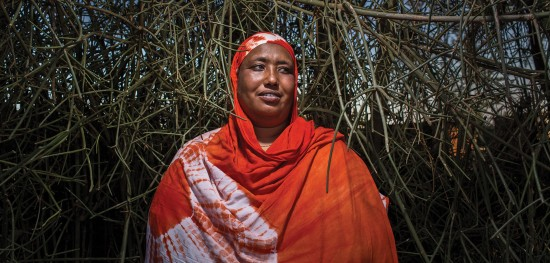 Nuria Gollo, the head of the Women Advocacy and Development Organization in Marsabit, poses for a portrait on her community's sacred land in northern Kenya. Research shows that over 90% of women in Marsabit county have suffered female genital mutiliation. Despite the practice being outlawed in 2008, it is still carried out in secret among many local communities.